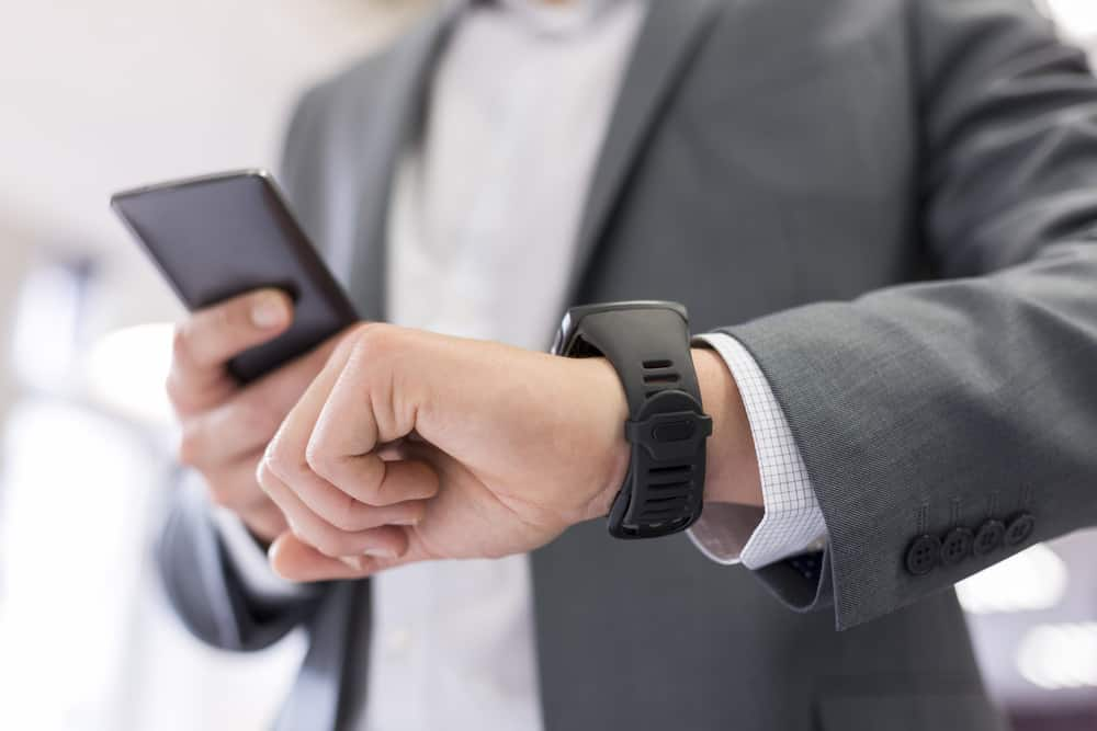 Man using smartwatch at work in office.