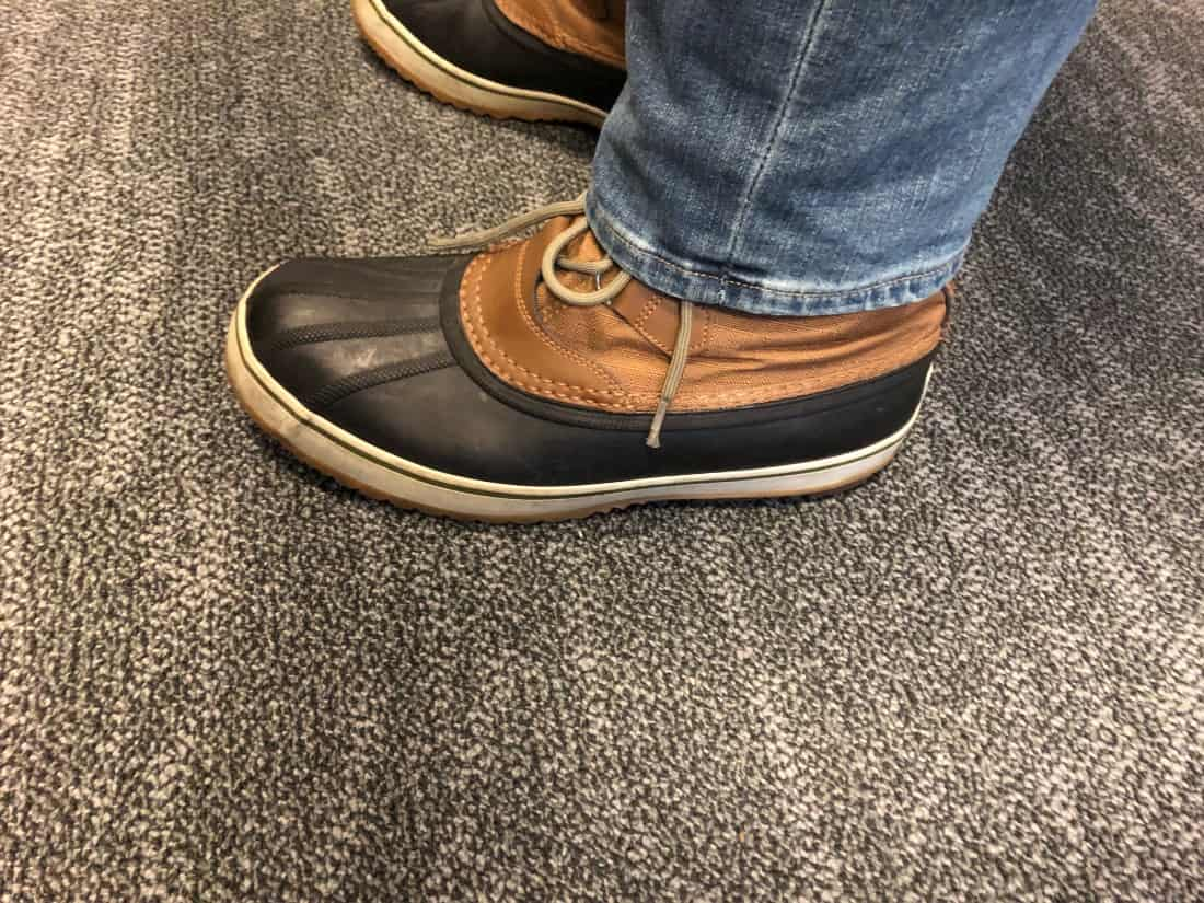 Side view of Sorel Caribou boots with jeans untucked.
