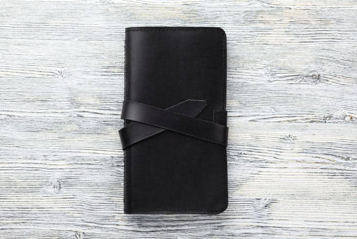 A black checkbook wallet with straps