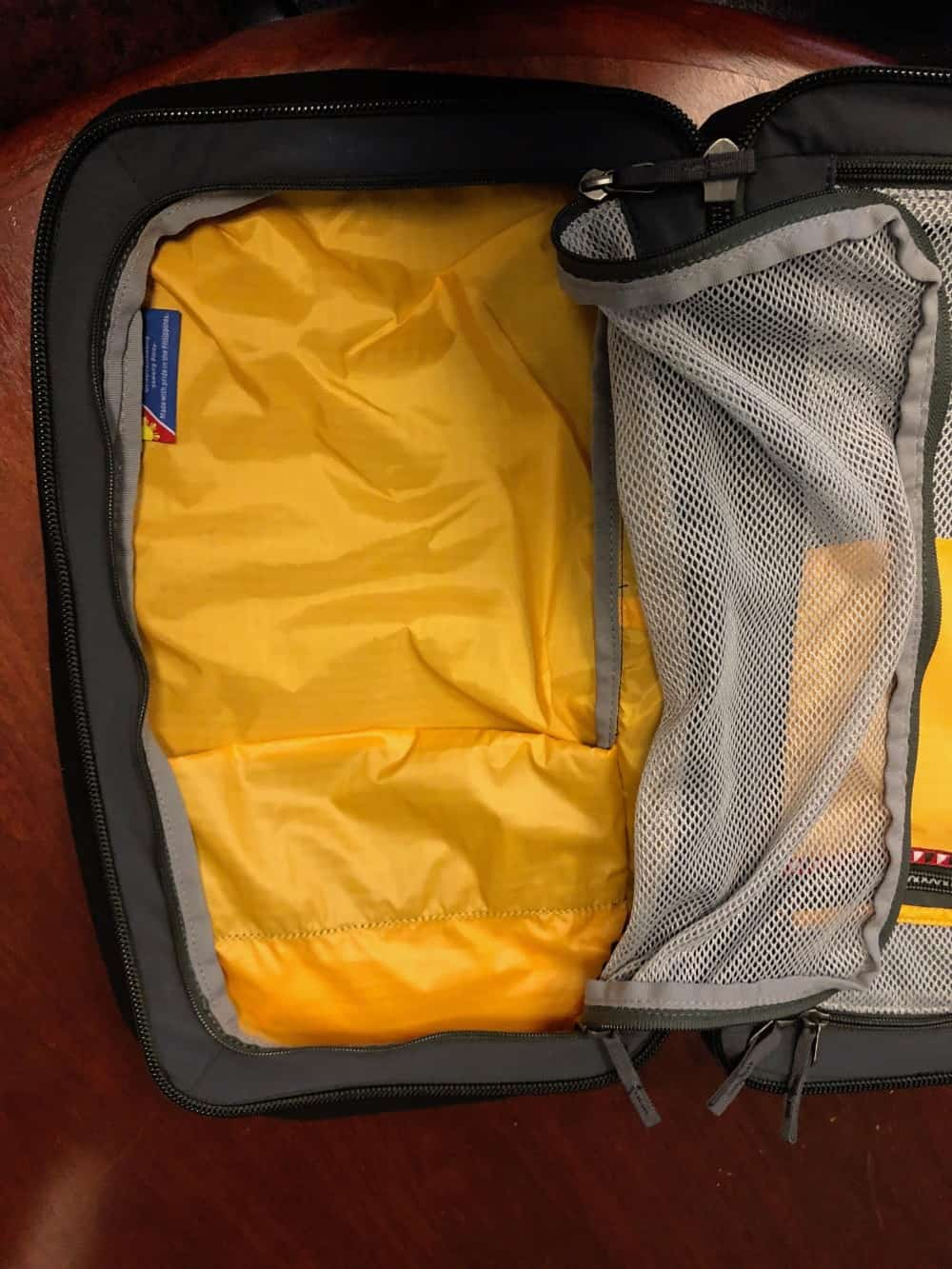 Left storage area with mesh covering unzipped on the Cotopaxi Nazca travel pack.
