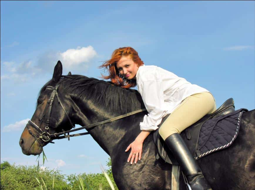A young woman wearing beige breeches or jodhpurs while horse riding