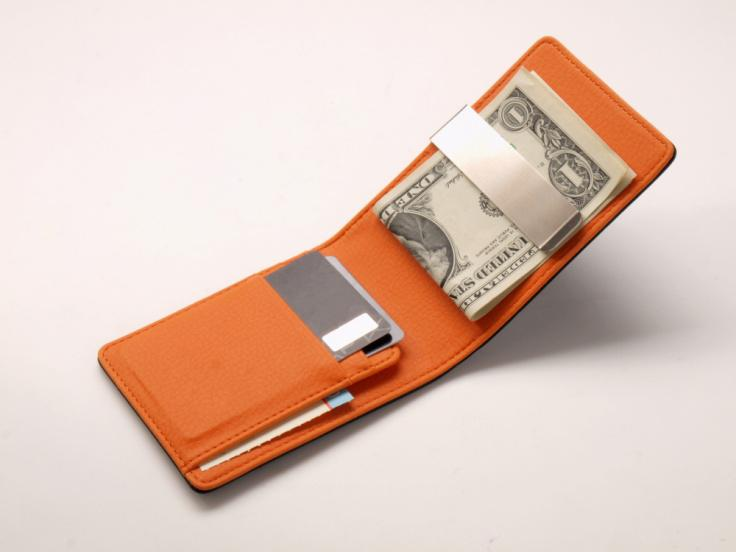 An orange money clip wallet with pockets