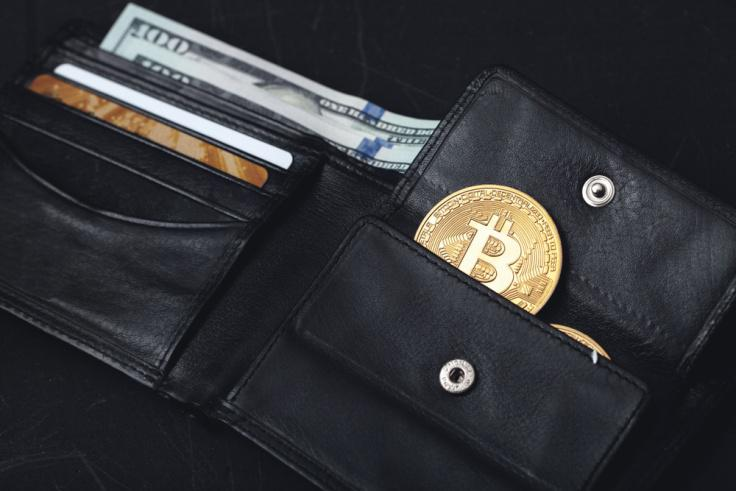 A black wallet with a coin slot