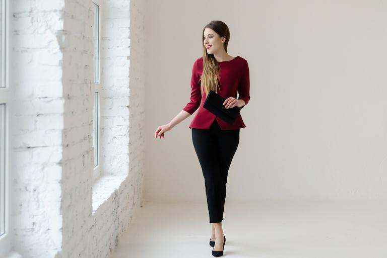 A young woman dressed in a dark red blouse and black tailored trousers