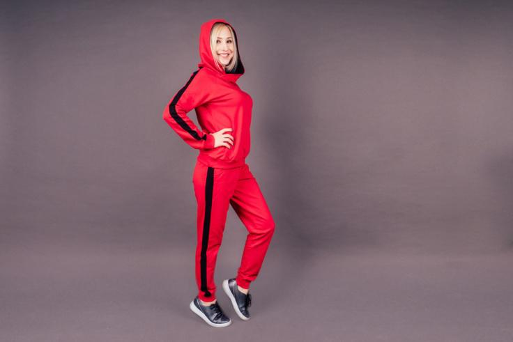 A blonde woman dressed in a red track suit with black stripe