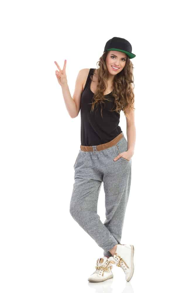 Model wearing a cap, tank top, hip-hop pants, and sneakers and posing with a peace finger sign.