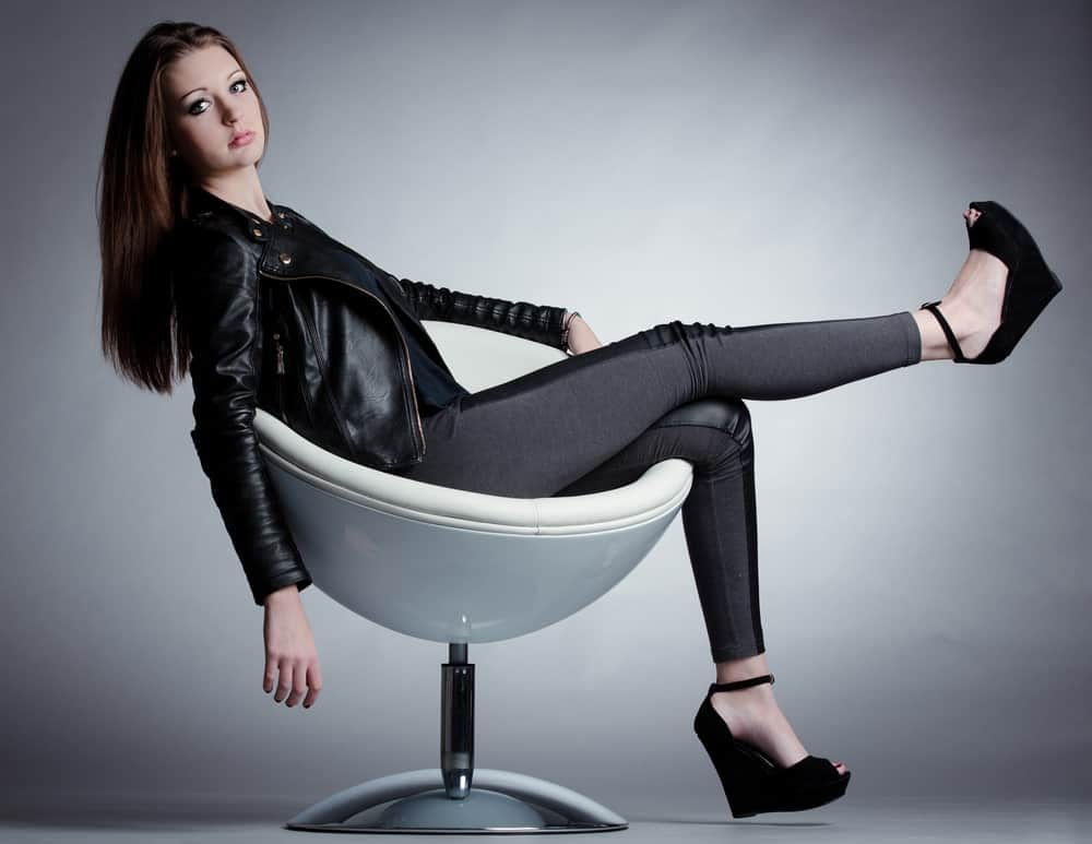 Model on a round chair wearing black leather jacket, jeggings, and heels.