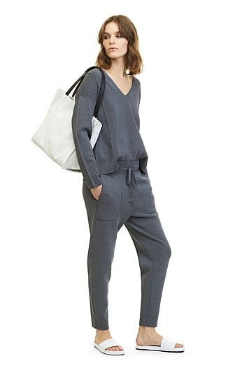 Model wearing a matching long sleeve top and stretch-knit pants with a tote shoulder bag.