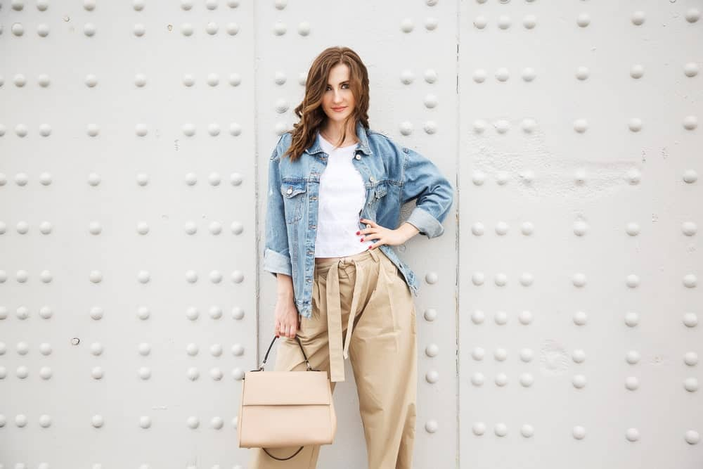 Model wearing a white shirt underneath a jeans jacket, wide-legged pants and holding a handbag.