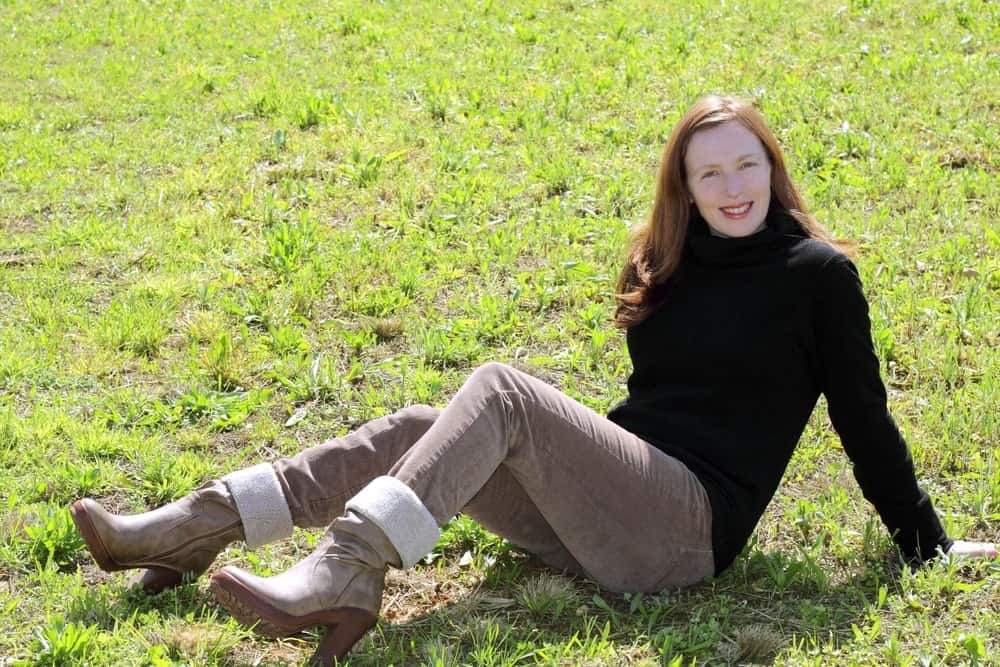 Woman on grass wearing turtleneck, corduroy pants, and boots.