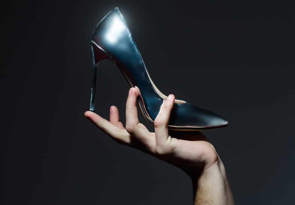 Hand holding up in the air a black stiletto heel.