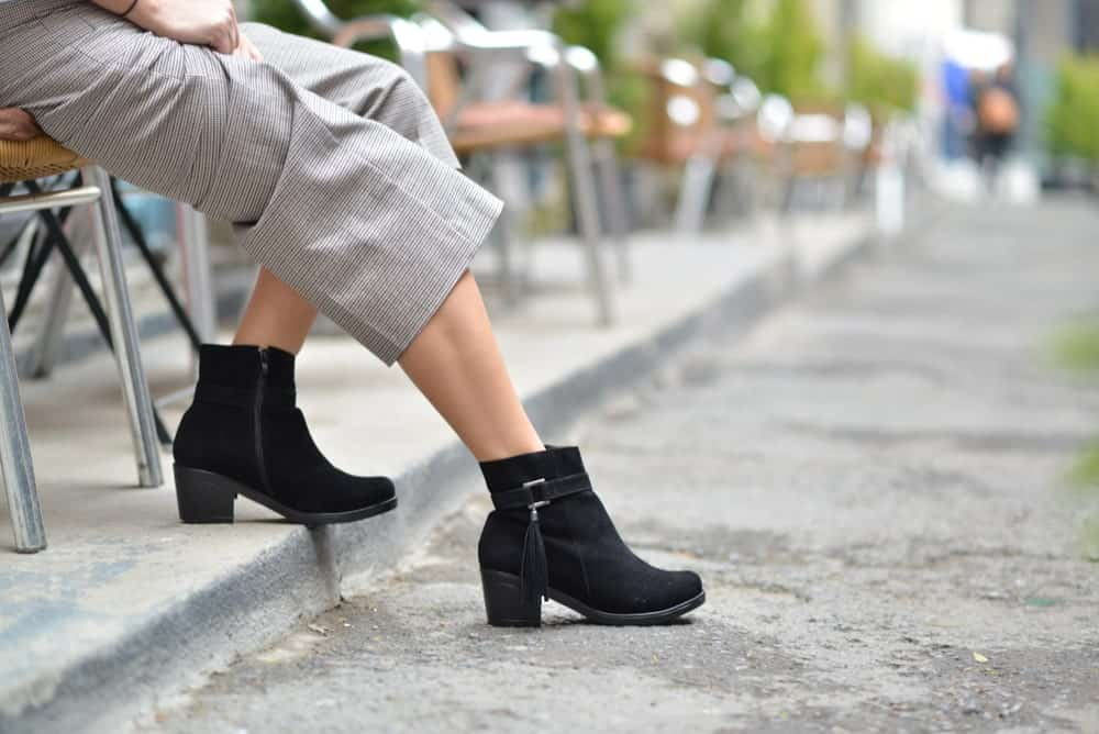 High-heeled boots worn with grey pants