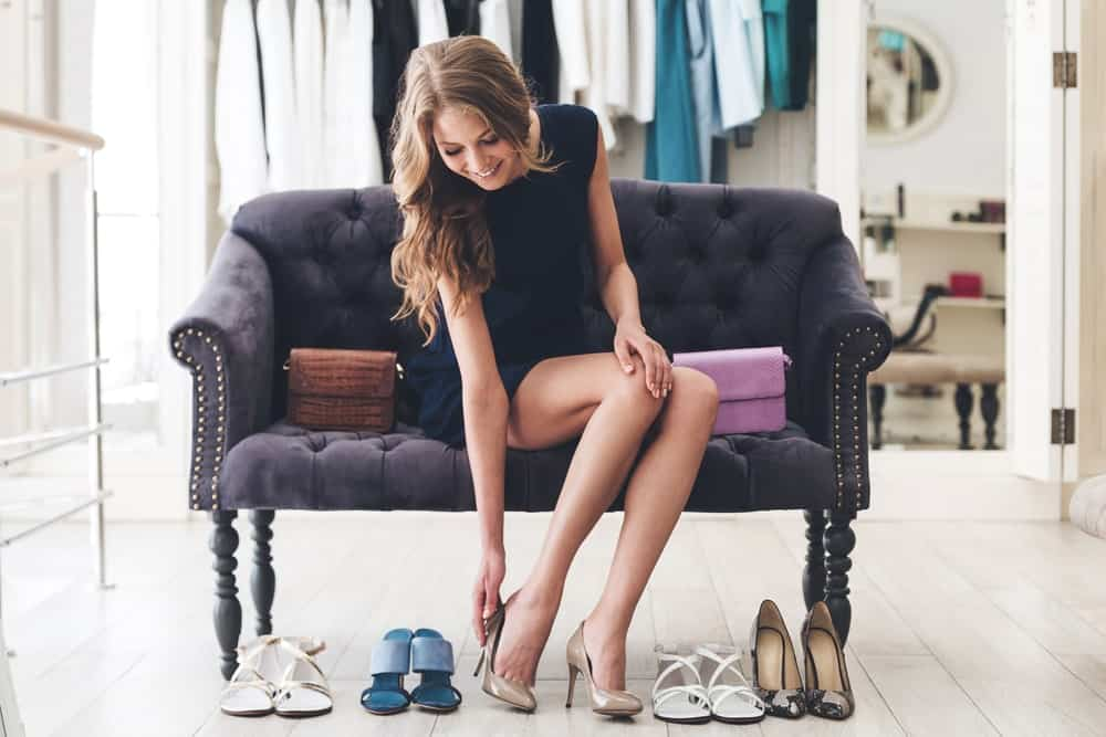 Woman trying on various pairs of shoes.