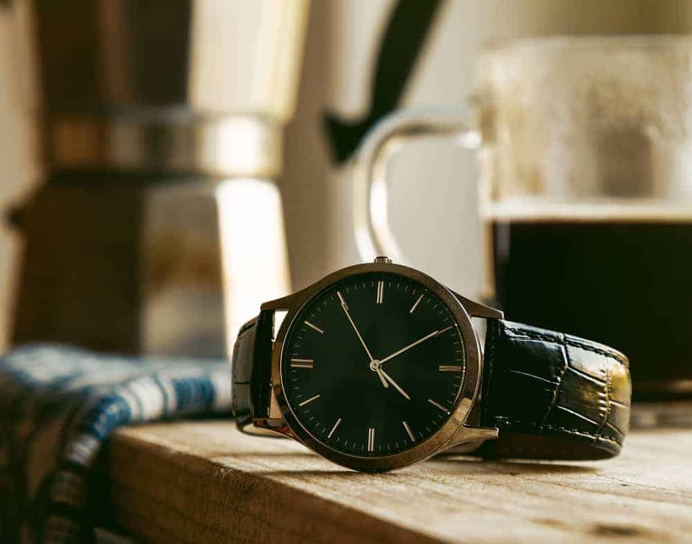 A round-shaped wristwatch for men with black straps.