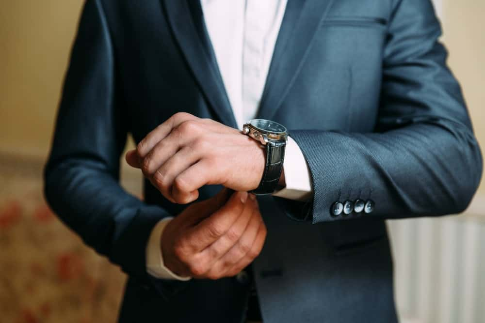 Cropped photo of a man in suit wearing a luxury wristwatch.