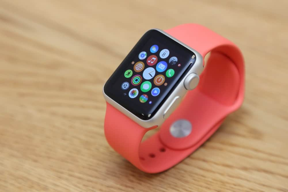 A close look at an Apple watch with a sporty pink watchband.