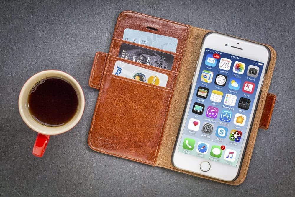 iPhone in wallet case beside a cup of coffee.