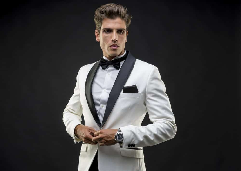 A young man in black bowtie, white tuxedo, and wristwatch against a black background.