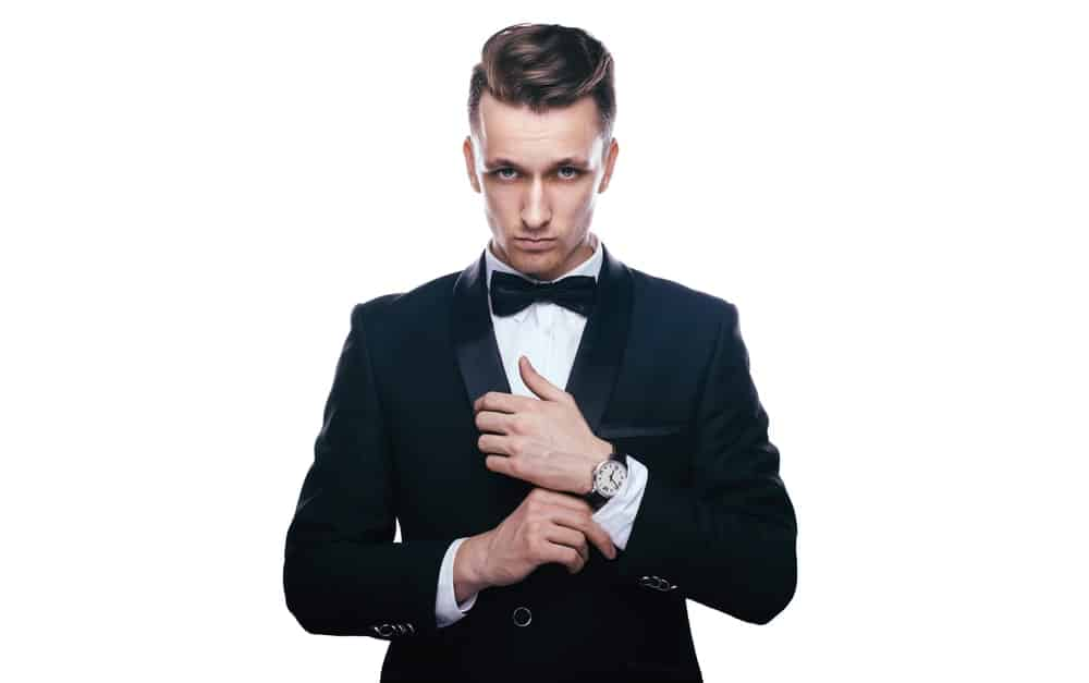 A young man holding in black bowtie, tuxedo, and wristwatch.