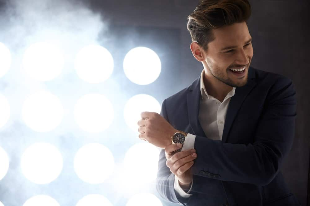 Side profile of a young man smiling and wearing a blue suit while holding his wristwatch.