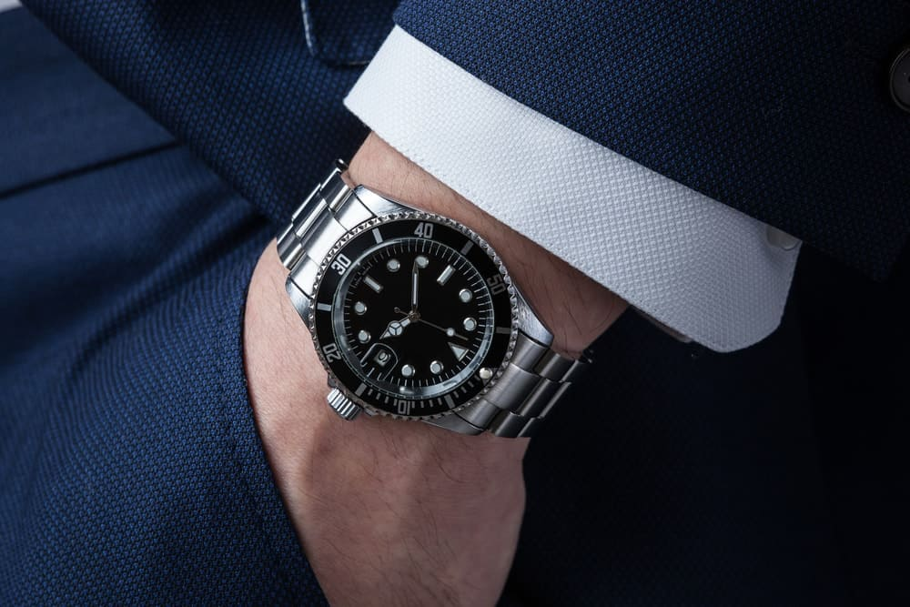 A close look at a man's left hand wearing a silver wristwatch.