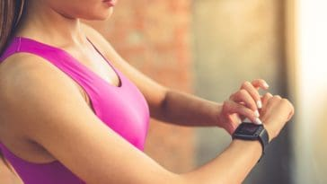A woman setting her smartwatch before her exercise.