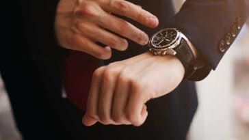 A close look at a man's watch and its black watchband.
