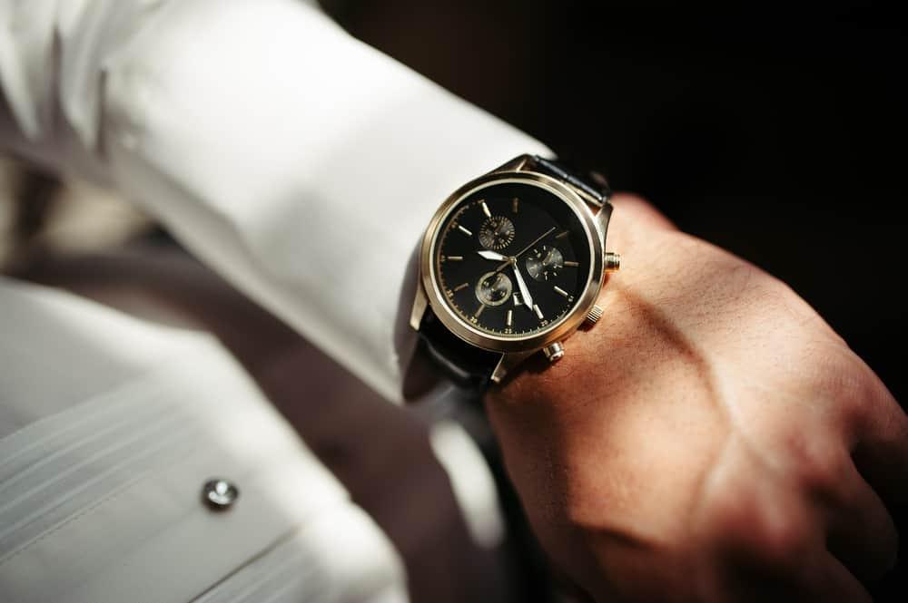 An elegant analog dress watch on a formally-dressed man.