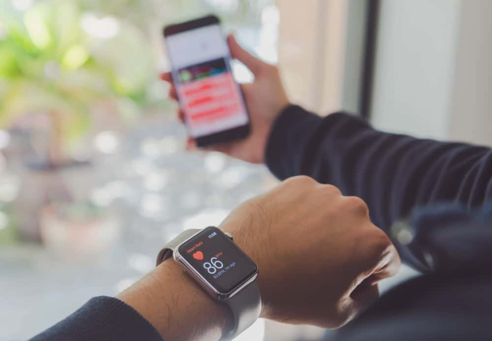 A man monitoring his heart rate with an Apple Watch and iphone.
