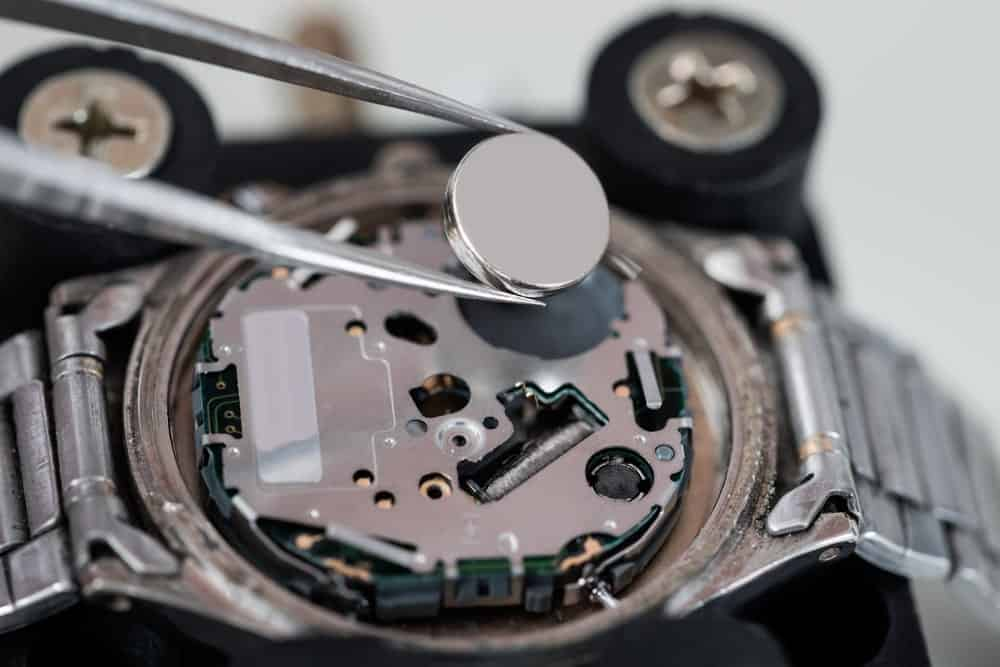 A wristwatch battery being installed with a pair of tweezers.