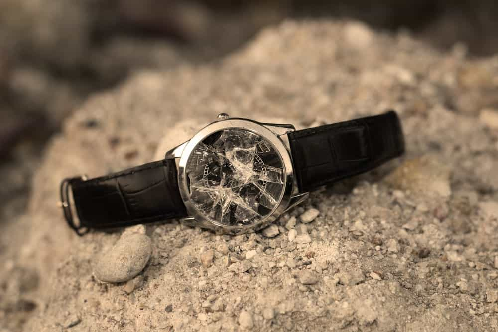 A look at a broken watch on a rocky ground.