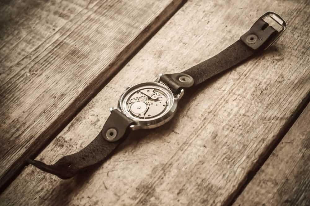 A broken wristwatch on a wooden background.