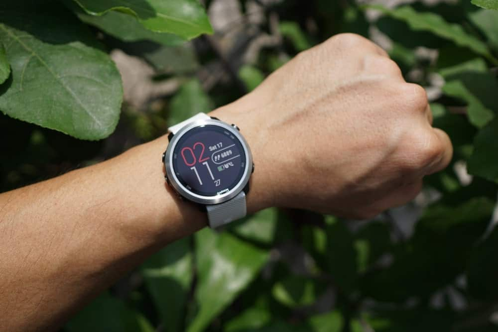 A Garmin watch worn by a man in an outdoor setting.