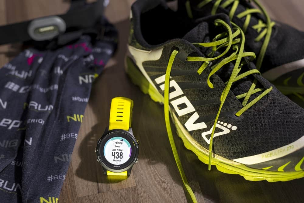 A Garmin watch in middle of running gear.