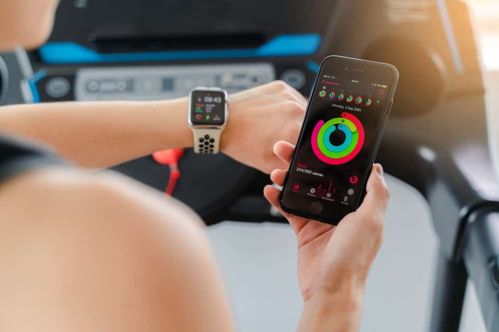 A woman man synchronizing her Apple watch with her phone before working out.