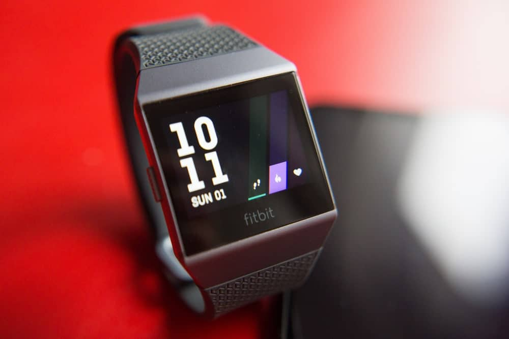 Fitbit ionic smartwatch against the red background.
