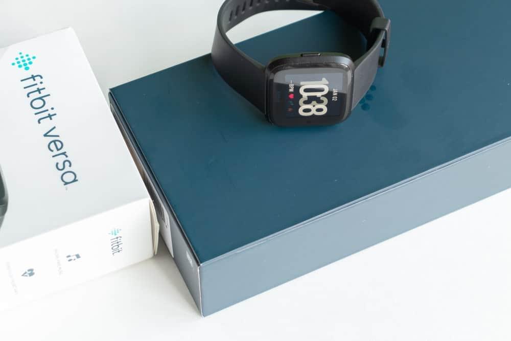 Black Fitbit versa on top of its original box.