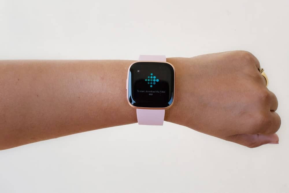 A woman wearing a Fitbit with pink straps.