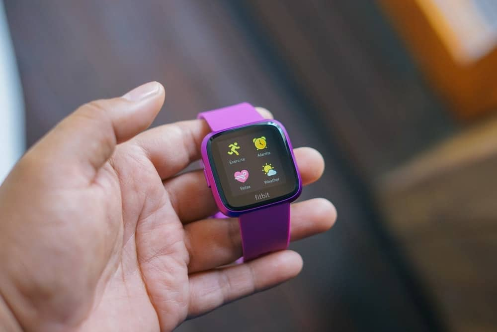 A close look at a Fitbit with purple straps.