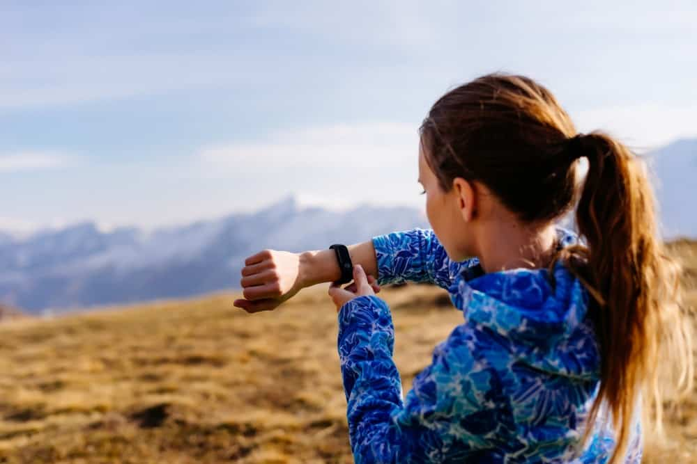 A woman on a jog checking her health tracker.