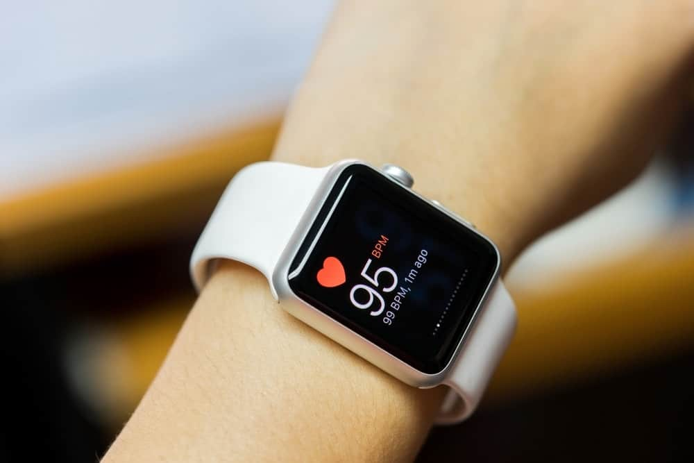 A woman wearing a smartwatch with white straps.