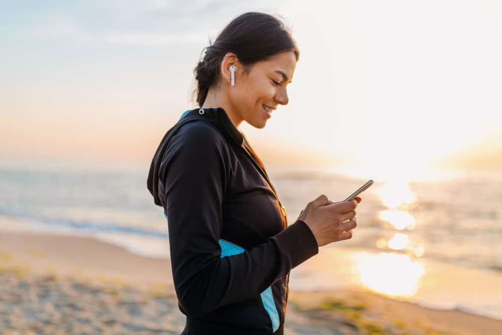 A woman jogging at beach while using wireless earbuds.