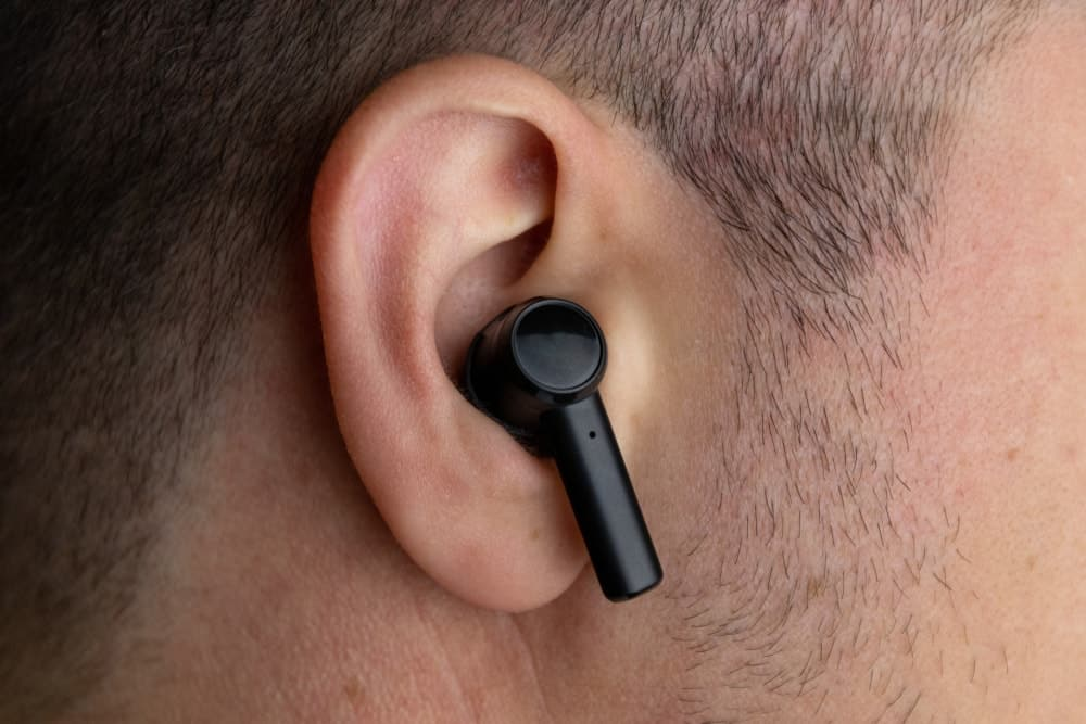 A close look at a man wearing a black wireless earbud on his right ear.