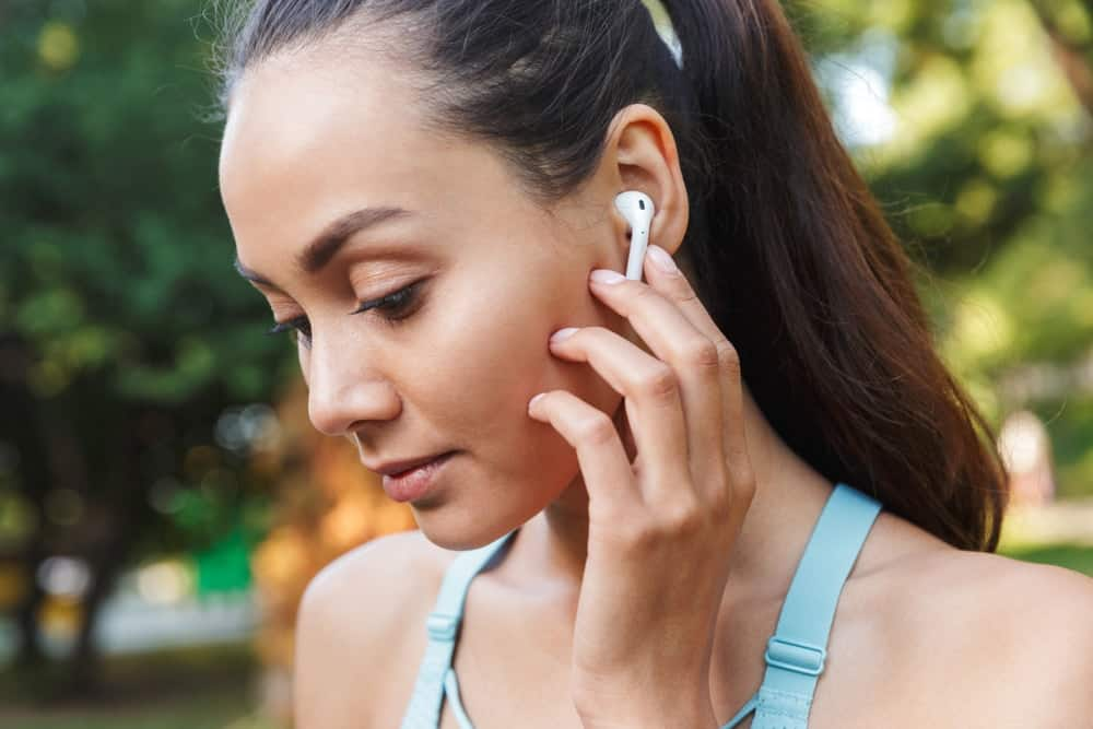 A woman setting up her wireless earbuds before jogging.