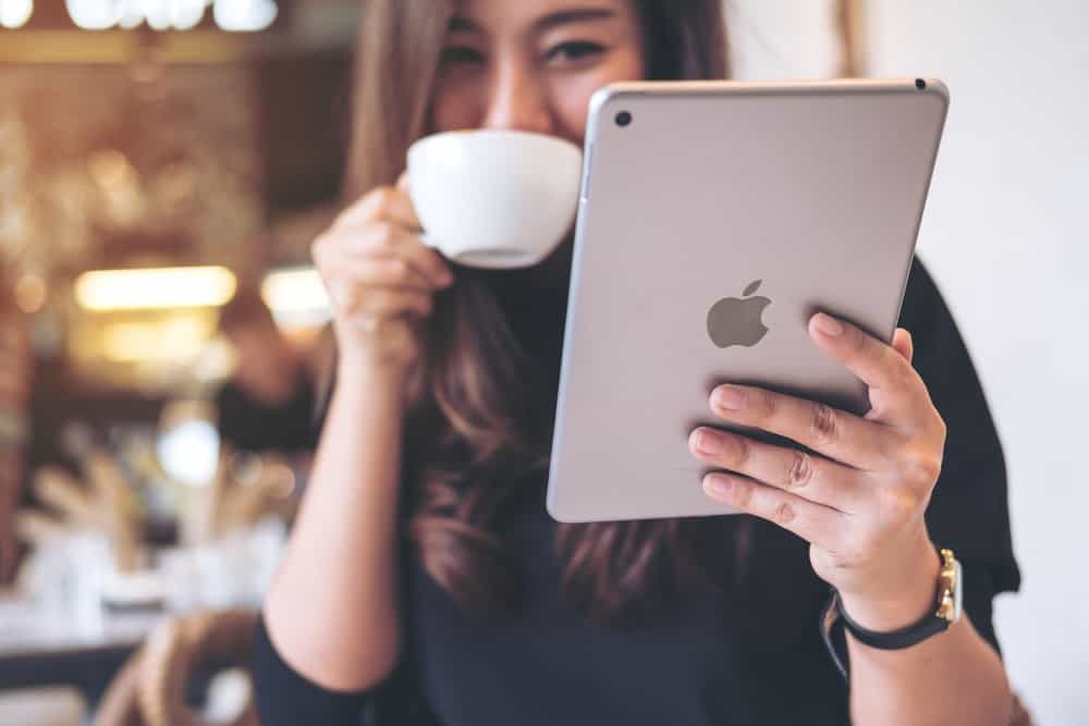 A woman using an iPad while drinking coffee.