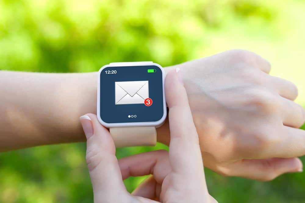 A close look at a woman checking her email on her smartwatch.