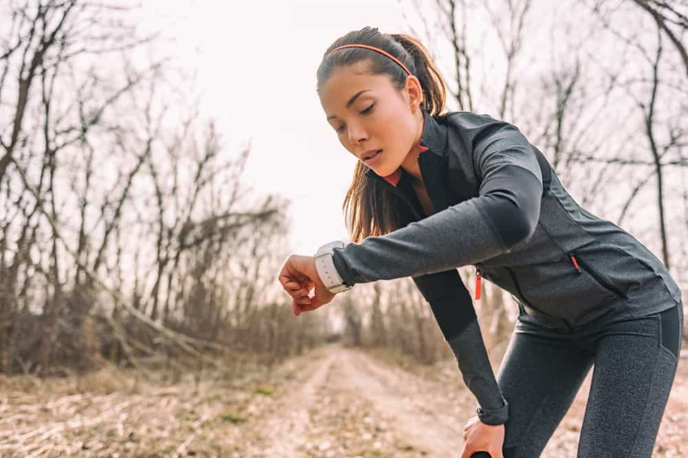 A female jogger checking her smartwatch health tracker.