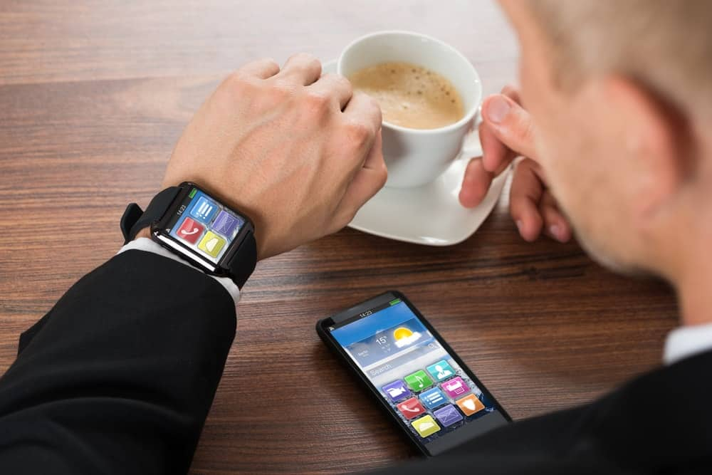 A businessman syncing his smartwatch with his phone apps.
