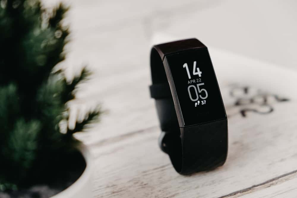 A close look at a brand new Fitbit on a wooden surface.