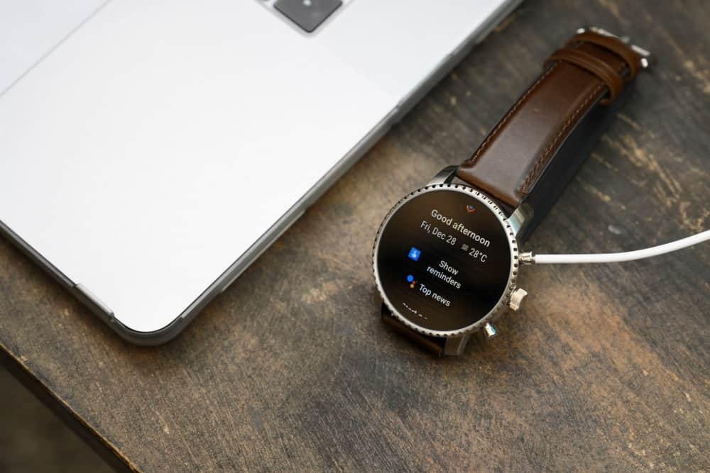 A close look at a smartwatch connected to the computer with a wire.